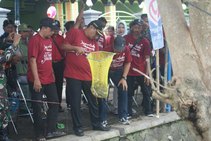 Bupati Syahri Mulyo (memegang keranjang ikan) saat membuka acara Mancing Bareng di Desa Gondosuli
